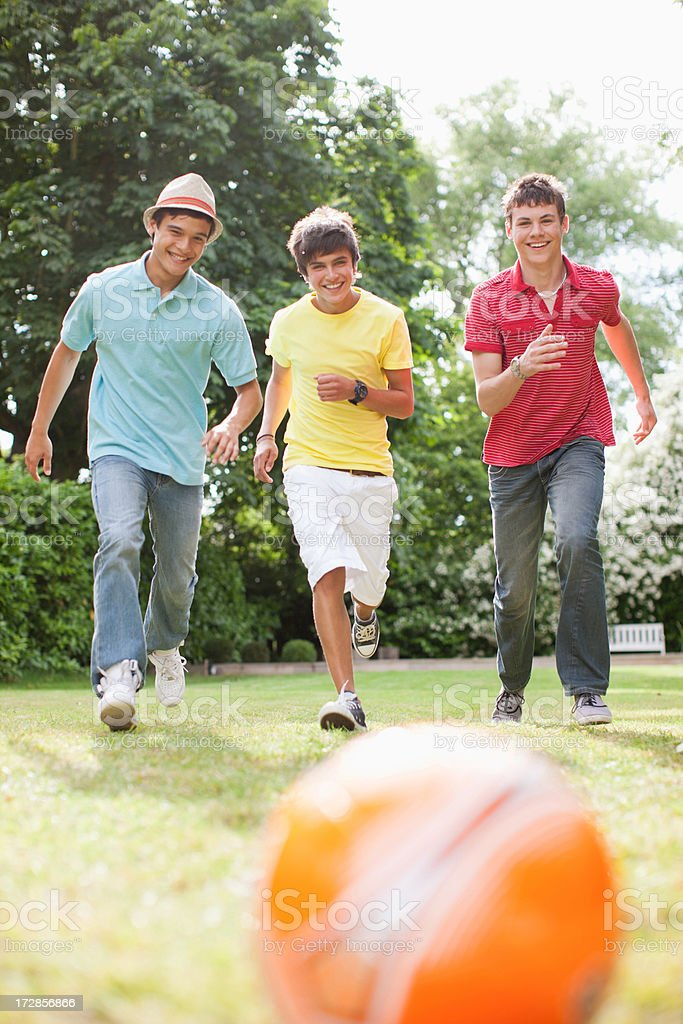 Teenage boys playing soccer together stock photo