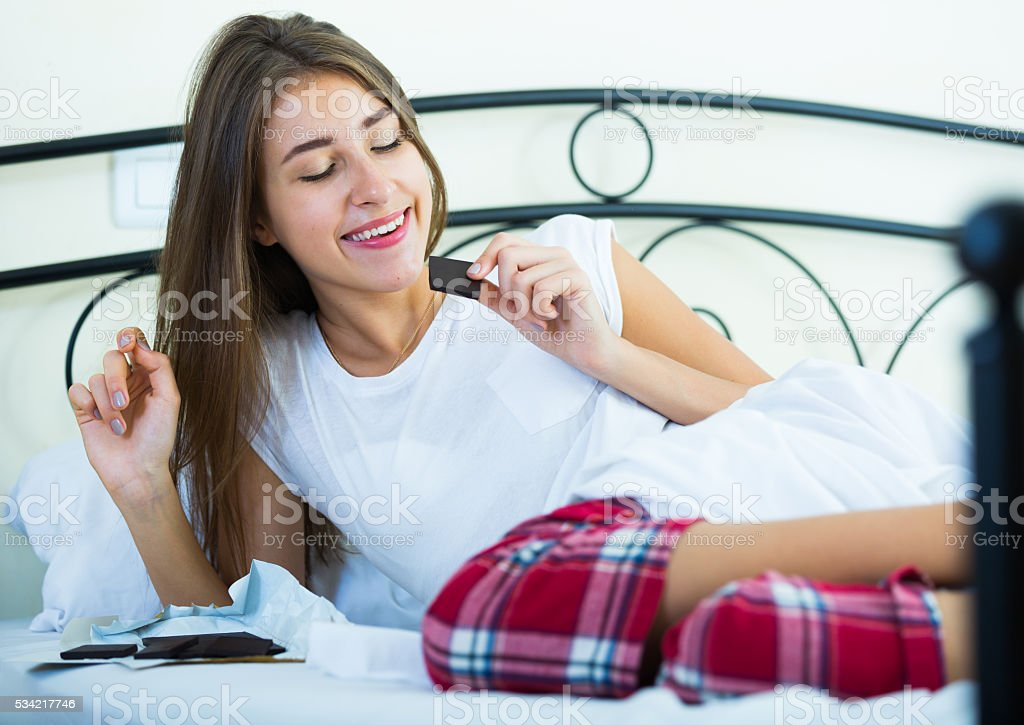 Teenage brunette enjoying chocolate bar in bed stock photo