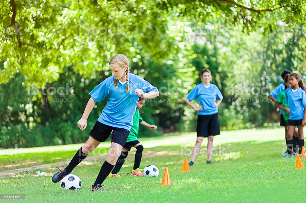 Teenage Caucasian soccer player kicks ball during practice stock photo