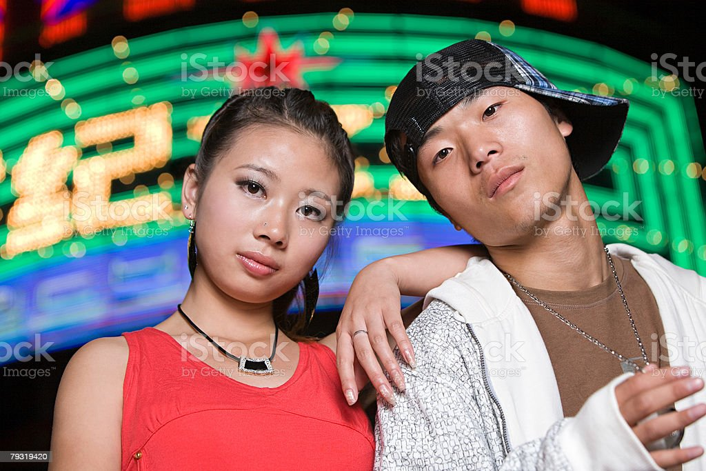Teenage couple by neon sign stock photo