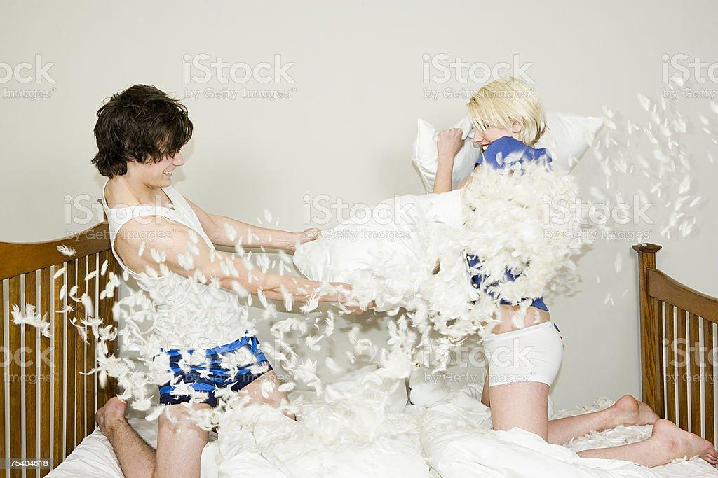 Teenage couple having a pillow fight stock photo