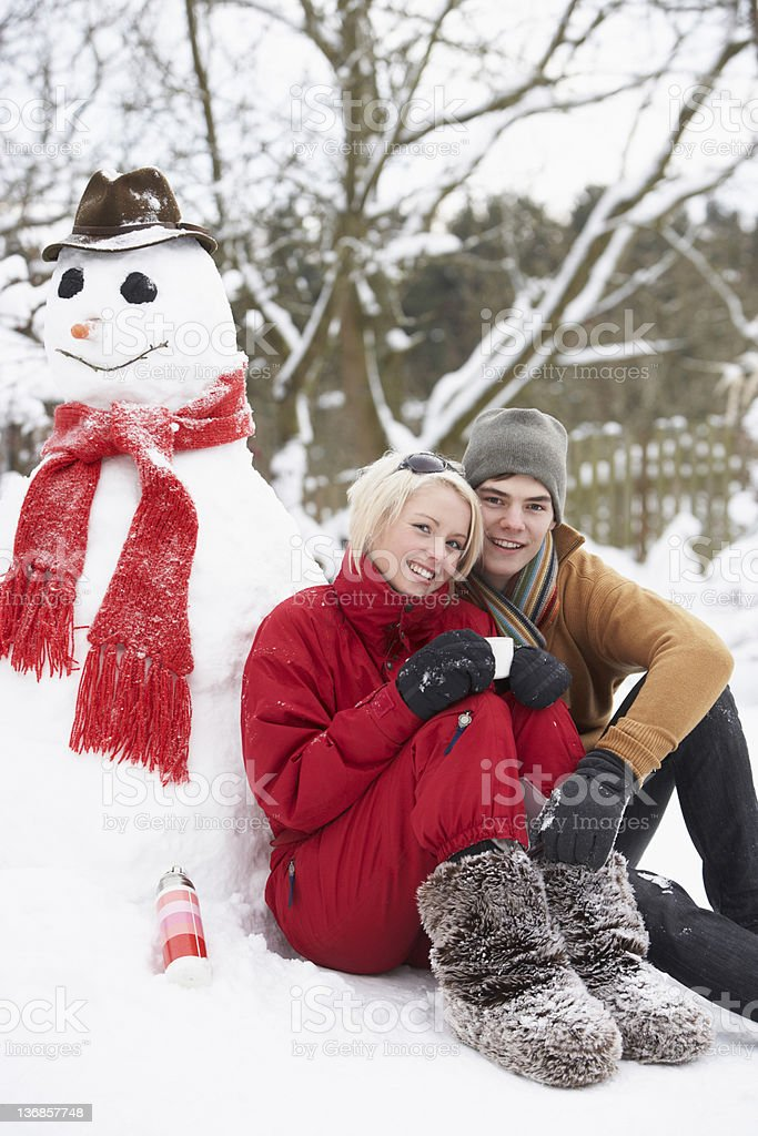 Teenage Couple In Winter Landscape Next To Snowman royalty-free stock photo