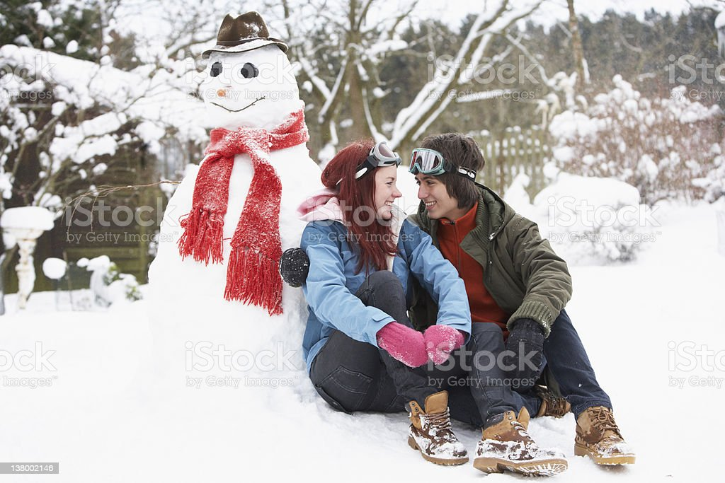 Teenage Couple In Winter Landscape Next To Snowman stock photo