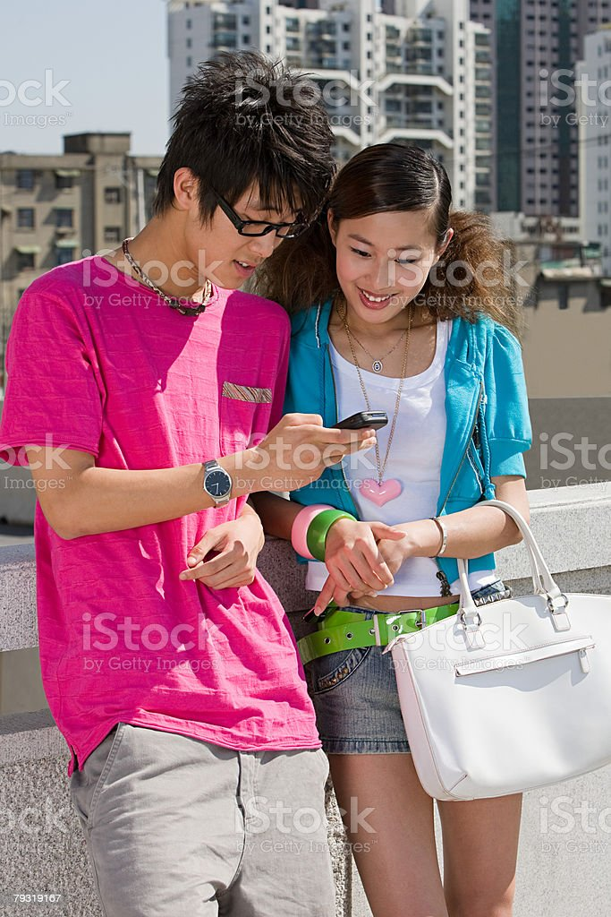 Teenage couple looking at cellphone royalty-free stock photo
