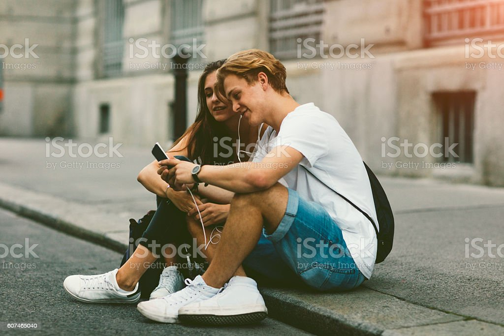 Teenage Couple Mobile Gaming Outdoors. stock photo