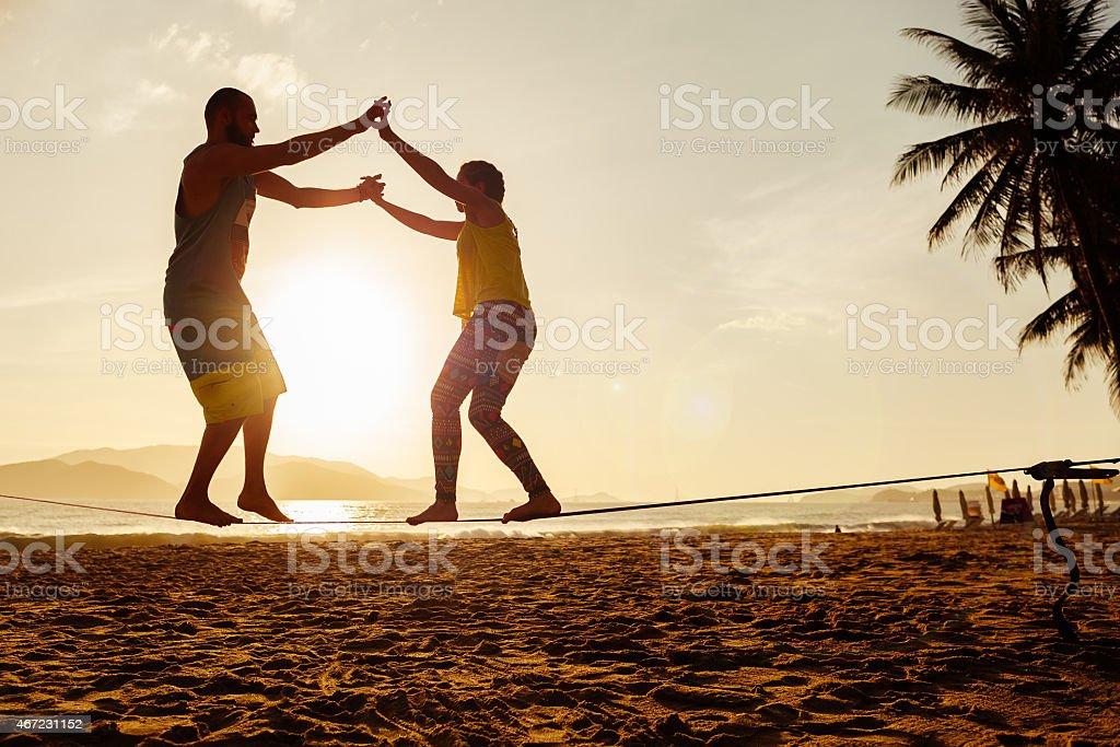 A teenage couple on the sand of a beach stock photo