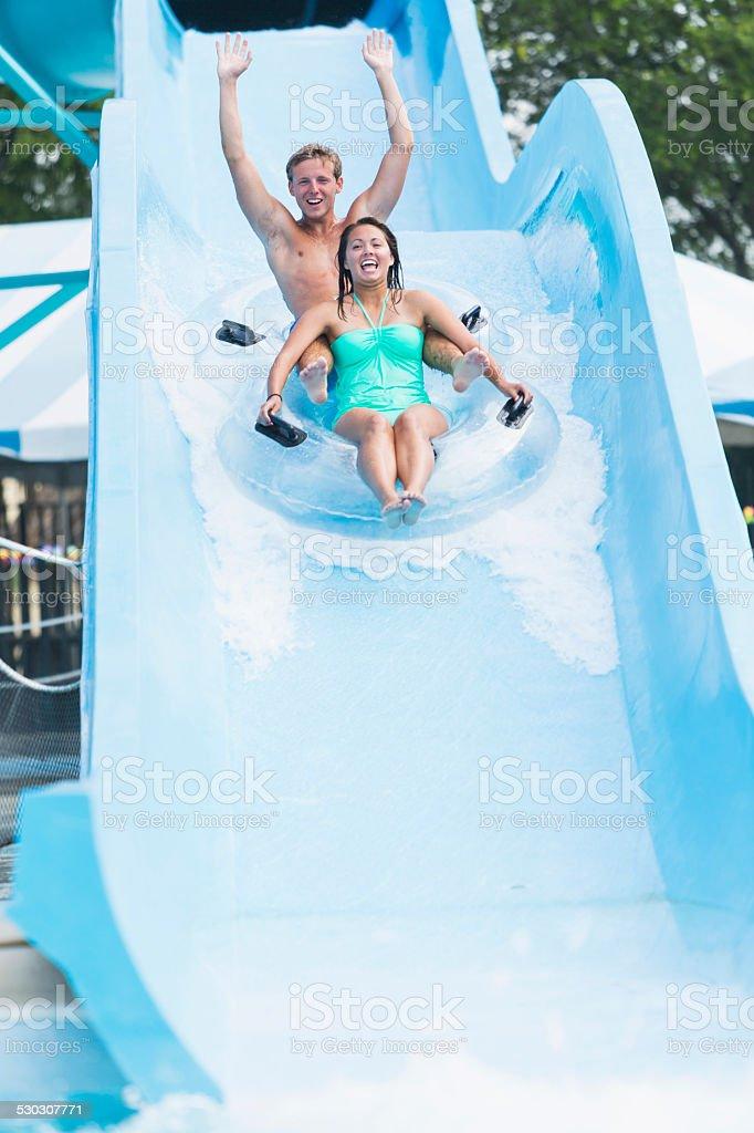Teenage couple on water slide at amusement park stock photo