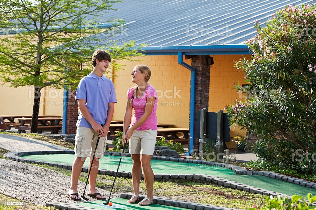 Teenage couple playing miniature golf royalty-free stock photo