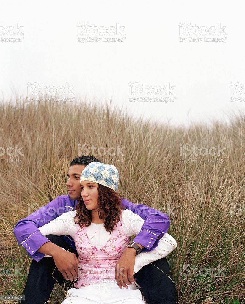 Teenage couple (16-18) sitting beside tall grass, looking away stock photo