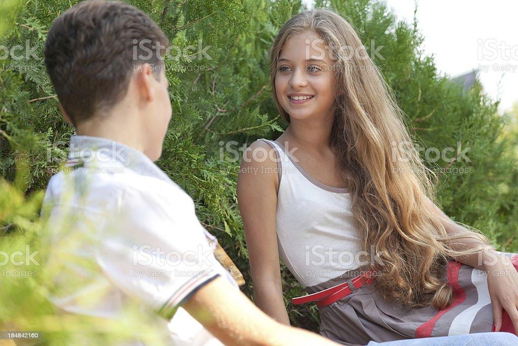 Teenage couple sitting in park,communicating stock photo
