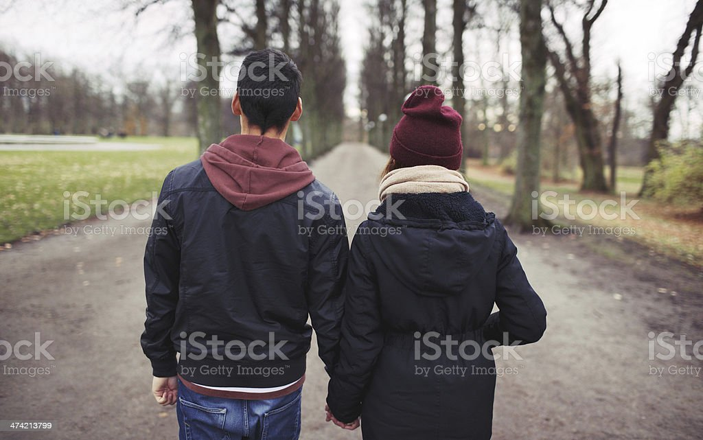 Teenage couple walking in park holding hands stock photo