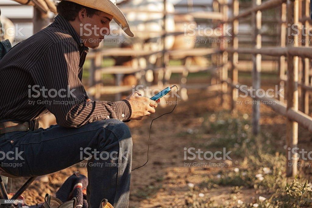 teenage cowboy on the cellphone stock photo