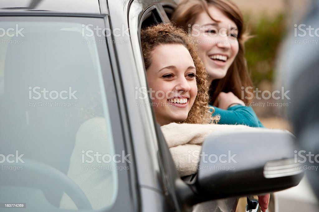 Teenage driver and friend leaning out car windows stock photo