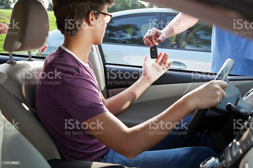 Teenage driver taking car keys stock photo