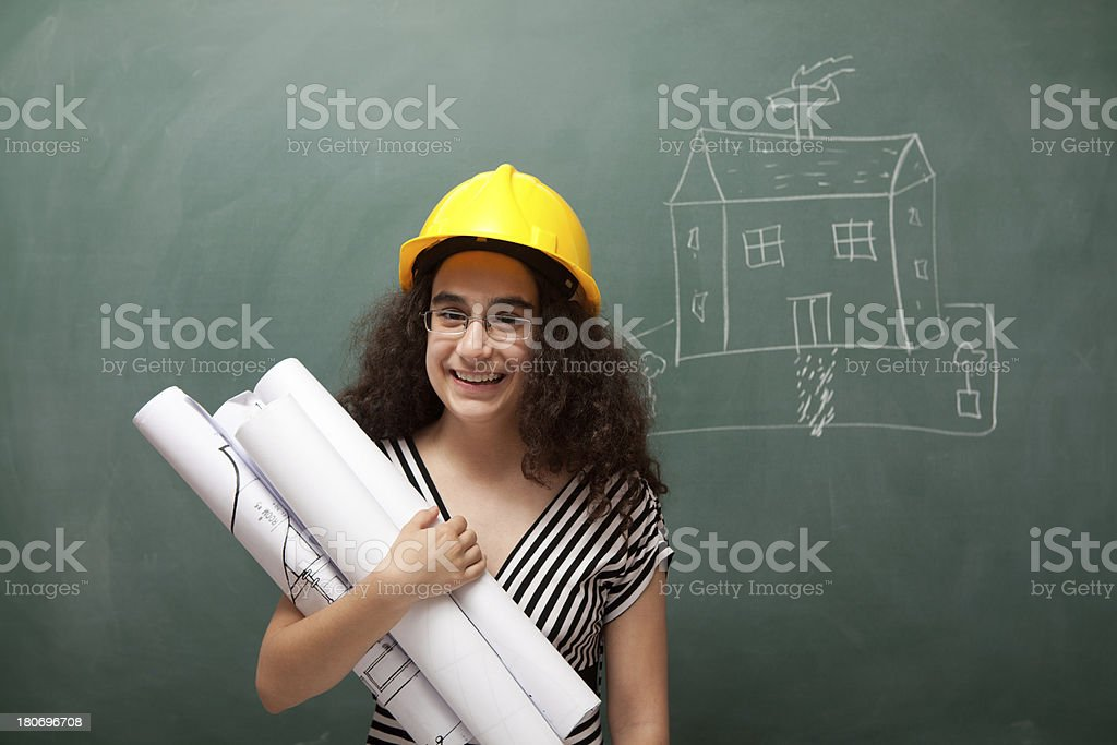 Teenage engineer with helmet holding blueprints royalty-free stock photo