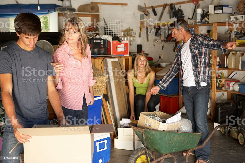 Teenage Family Clearing Garage For Yard Sale stock photo