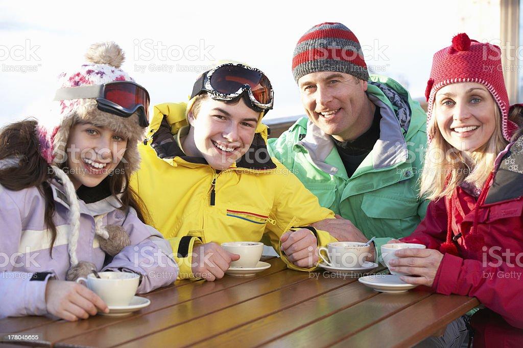 Teenage Family Enjoying Hot Drink In Café At Ski Resort stock photo