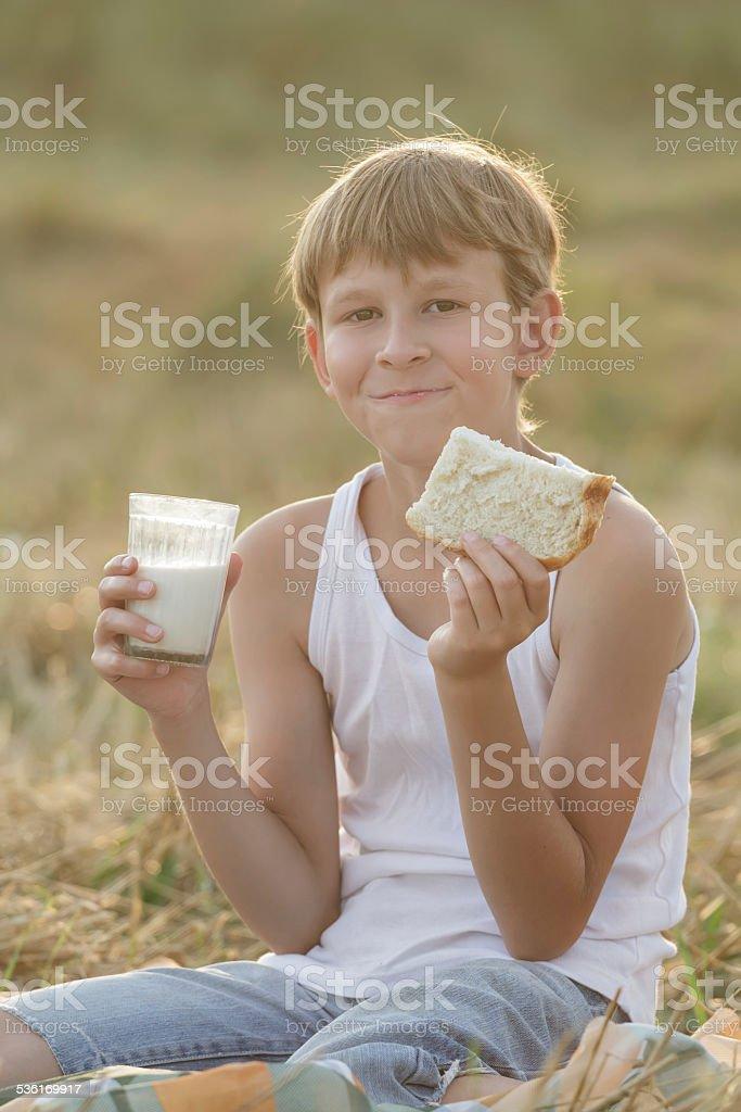 Teenage farmer boy holding milk and bread stock photo