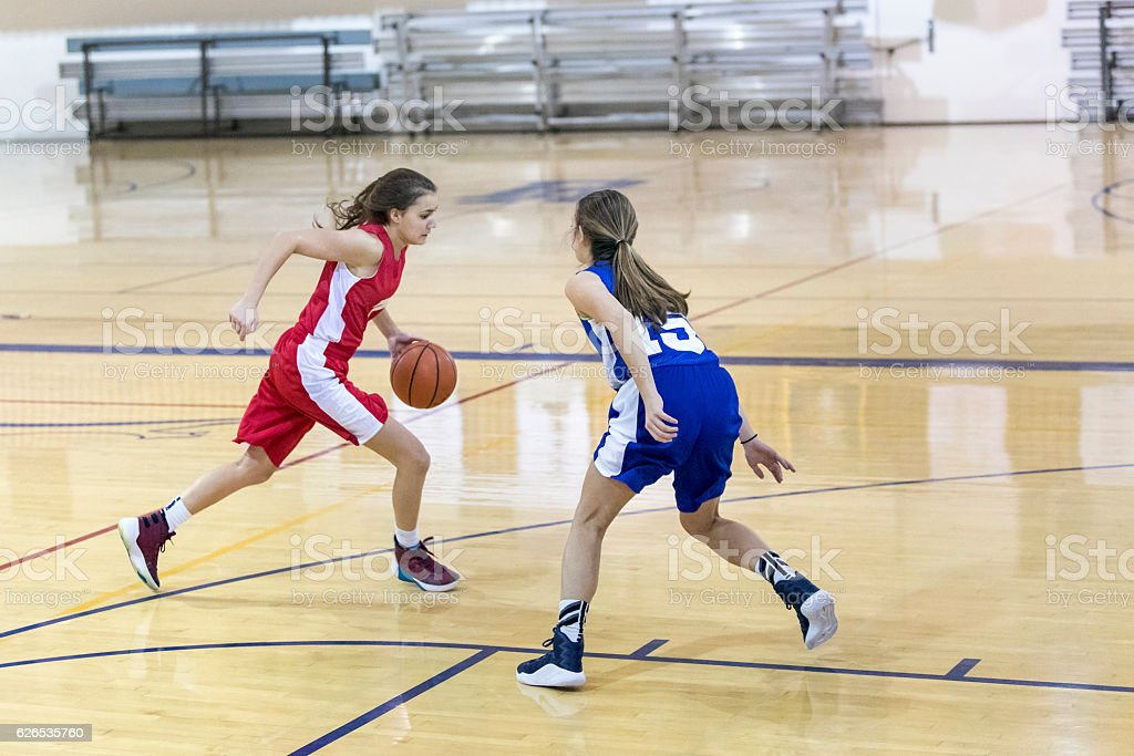 Teenage female basketball player one on one against another girl stock photo