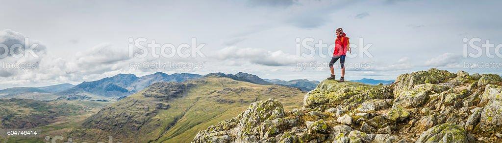 Teenage female hiker on rocky mountain summit overlooking peak panorama stock photo