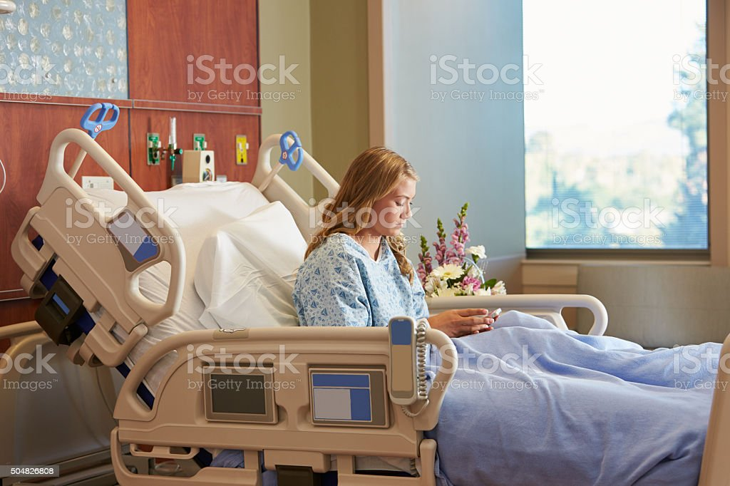 Teenage Female Patient In Hospital Bed Using Cellphone stock photo