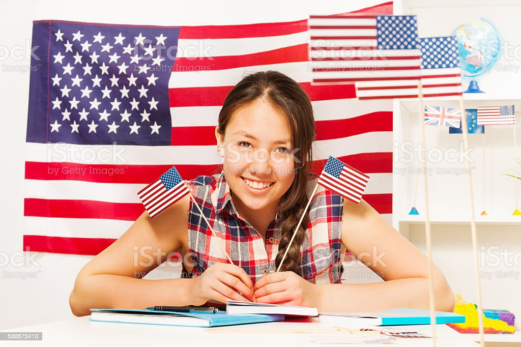 Teenage female student with two flags of USA stock photo
