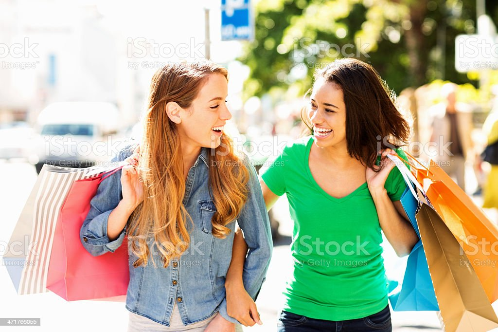 Teenage Friends Carrying Shopping Bags While Walking On Street royalty-free stock photo