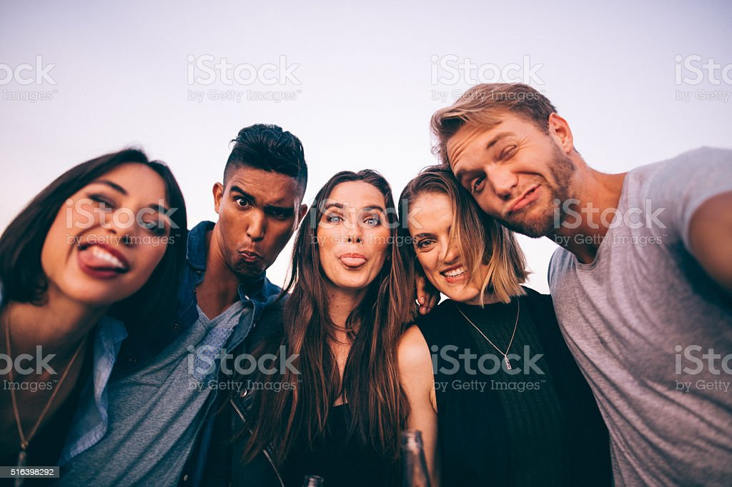 Teenage friends grimacing while taking a selfie stock photo