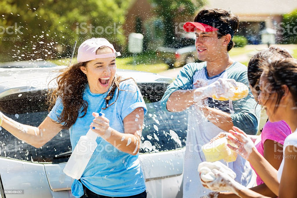 Teenage friends have water fight during car wash stock photo