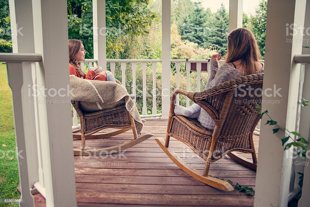 Teenage friends having hot drinks on country home porch autumn. stock photo