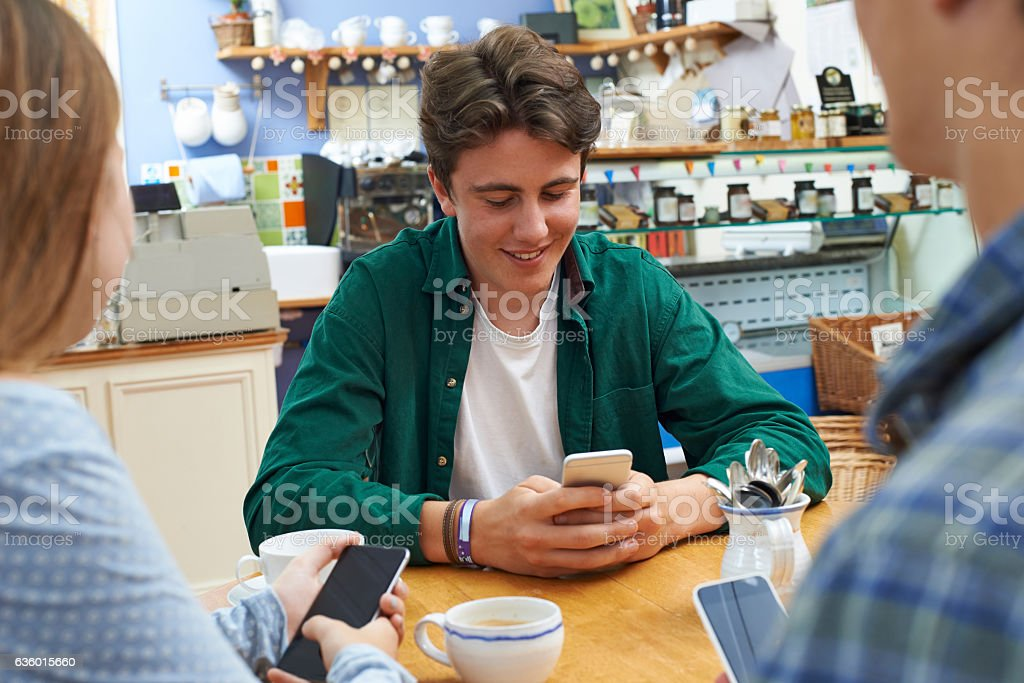 Teenage Friends Meeting In Cafe And Using Mobile Phones stock photo