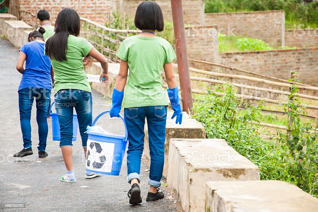 Teenage friends picking up trash to recycle. Roadside setting. stock photo