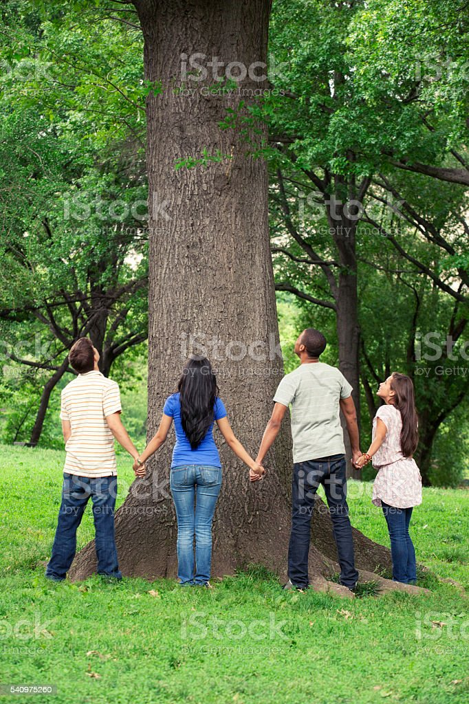Teenage friends spending time together at tree stock photo