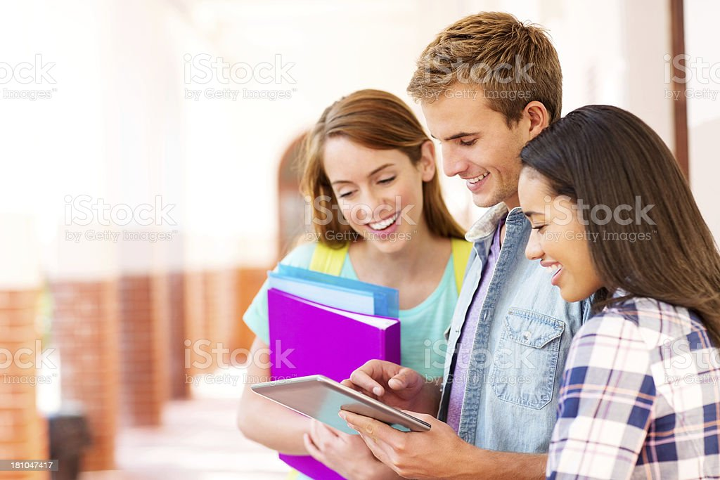 Teenage Friends Using Digital Tablet In College Campus royalty-free stock photo
