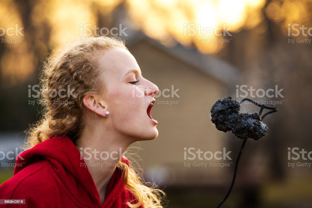 Teenage girl about to eat roasted marshmallow stock photo