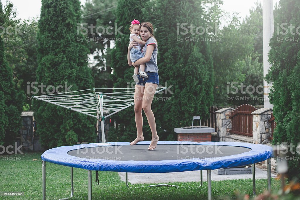 Teenage girl and baby playing on trampoline stock photo