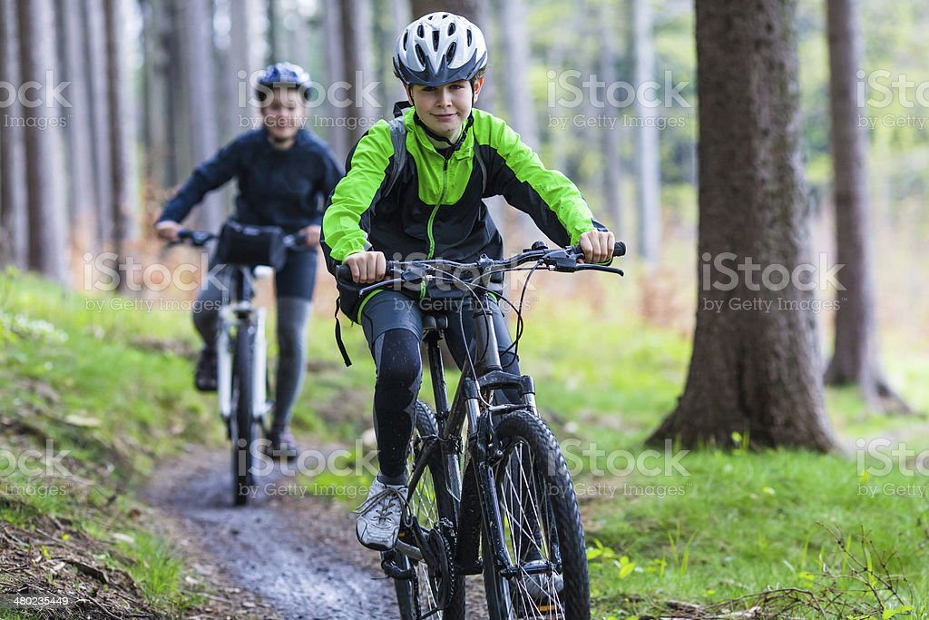Teenage girl and boy biking on forest trails royalty-free stock photo