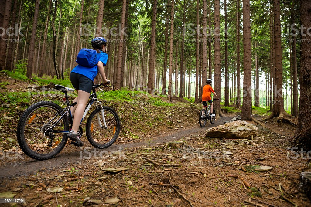 Teenage girl and boy biking on forest trails stock photo