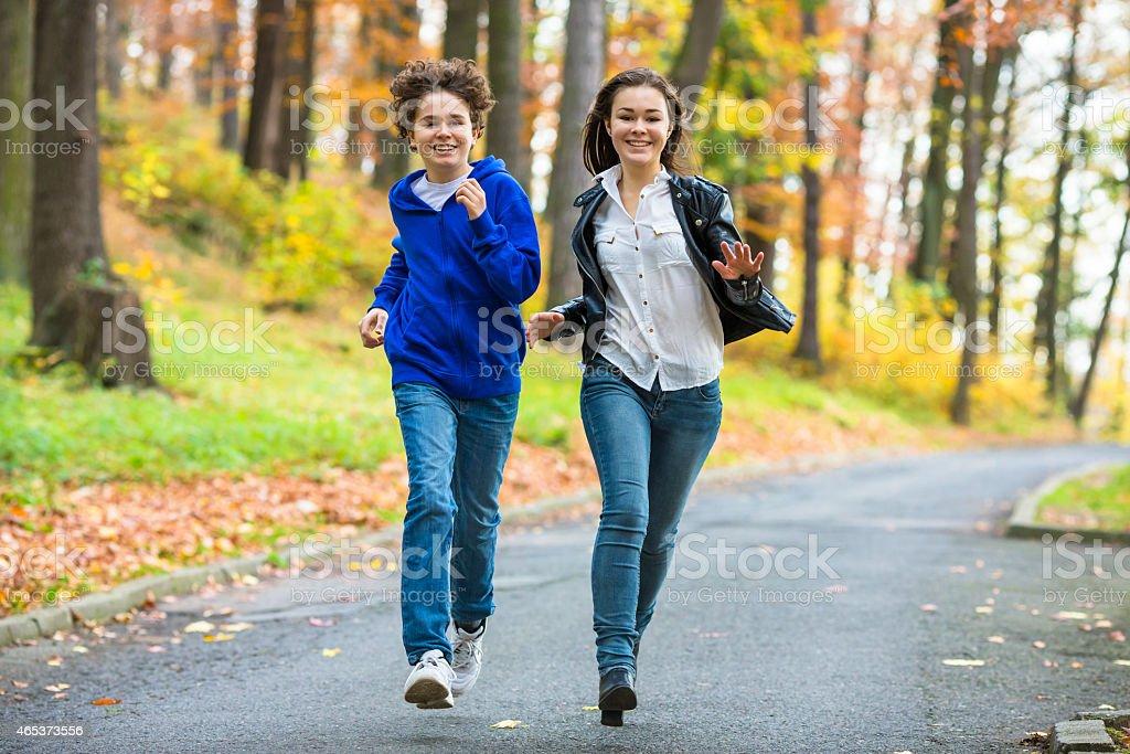 Teenage girl and boy running outdoor stock photo