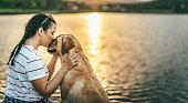 Teenage girl and her dog enjoying sunset by the lake