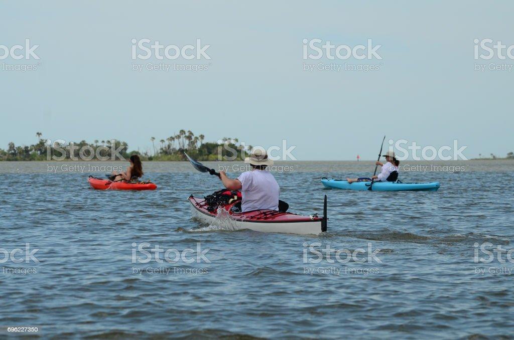Teenage girl and man paddling with mom paddling near palm islands stock photo