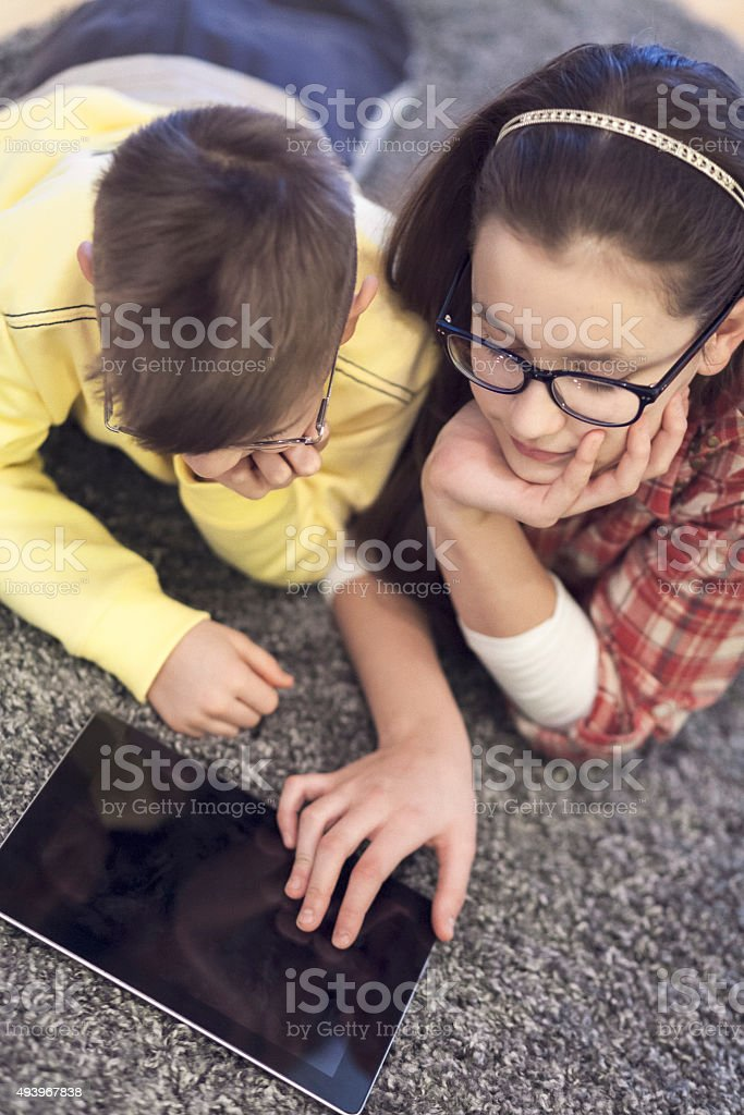 Teenage girl and young boy are playing with tablet stock photo