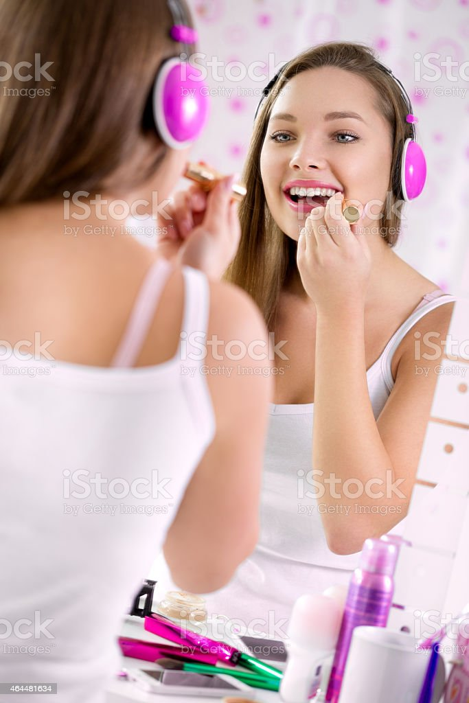 Teenage girl applying make up and looking in the mirror, stock photo