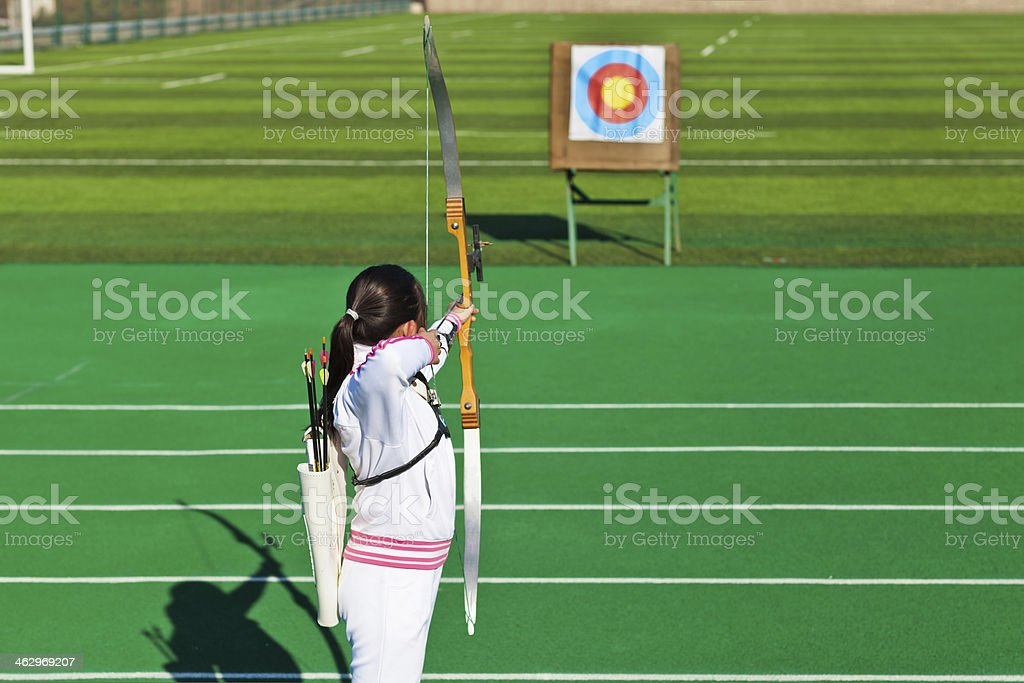 teenage girl archer aiming at target stock photo