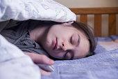 Teenage girl asleep holding mobile phone in her living room