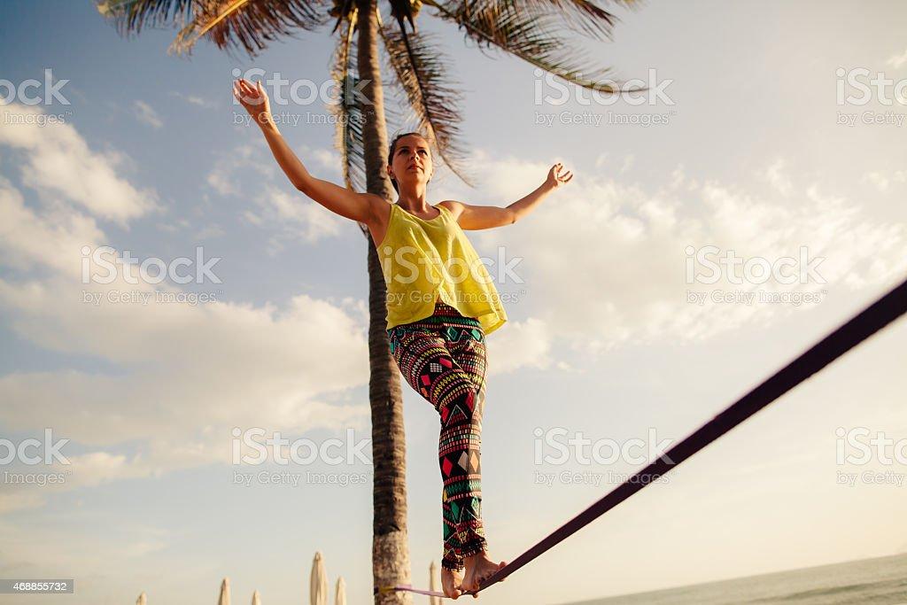 A teenage girl balancing on a rope beneath the sunny skies stock photo