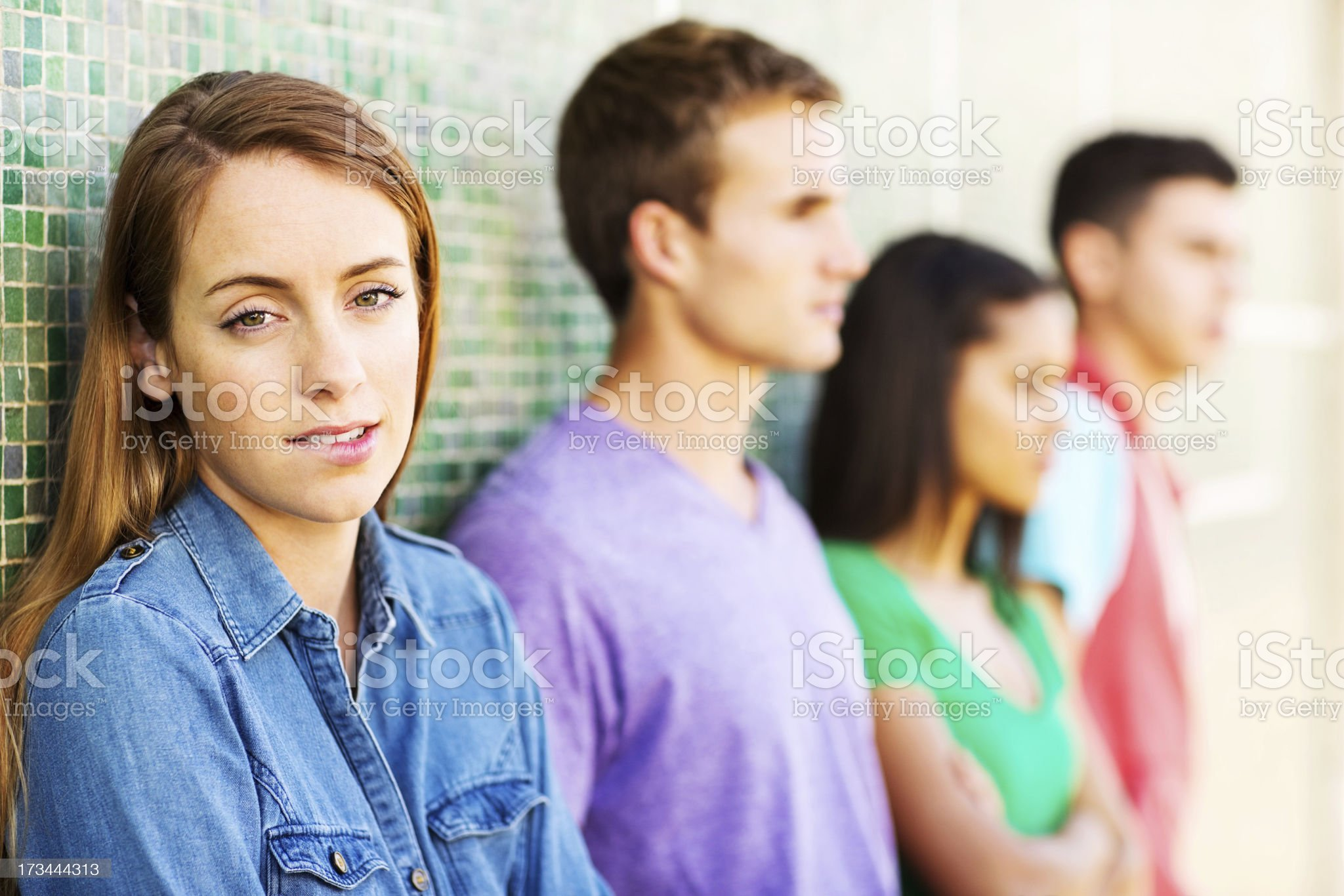 Teenage Girl Biting Lips With Friends Leaning On Wall royalty-free stock photo