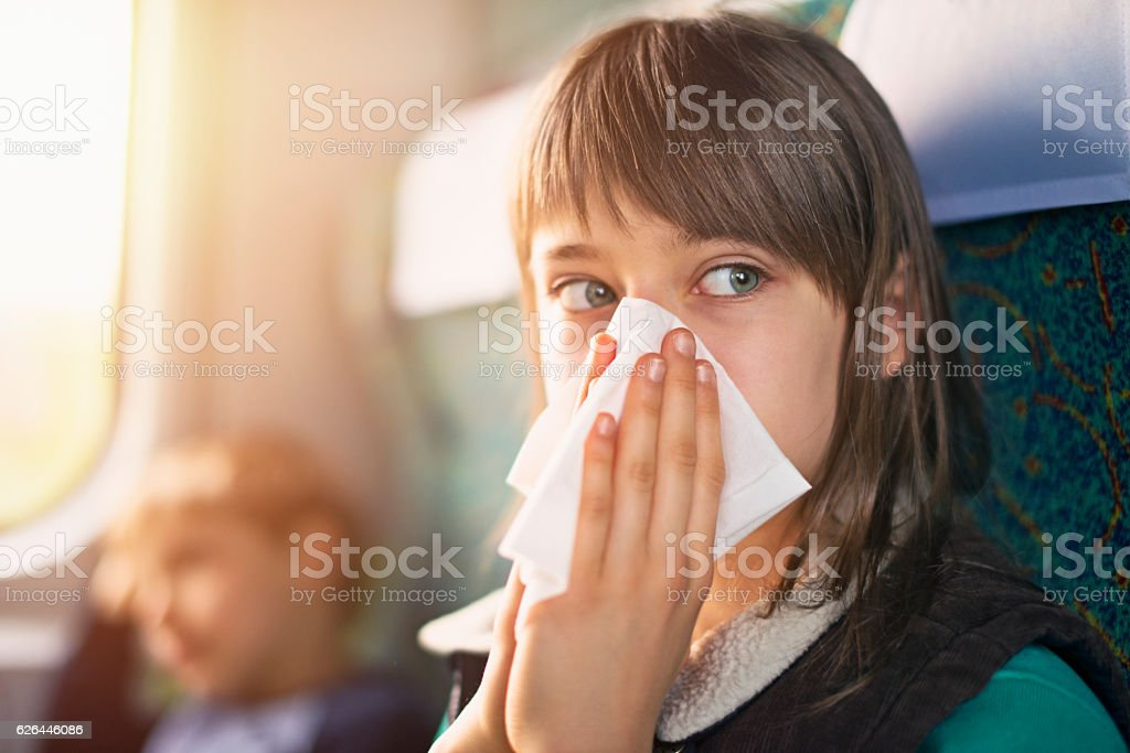 Teenage girl blowing nose on train stock photo