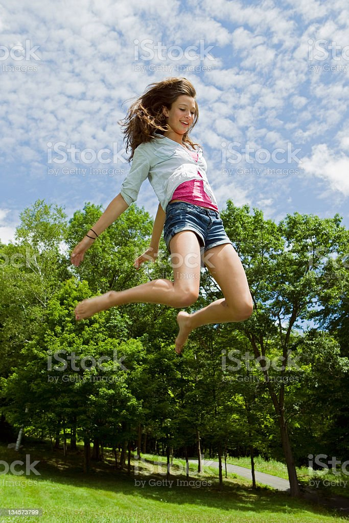 Teenage girl bouncing high in the air in the countryside stock photo