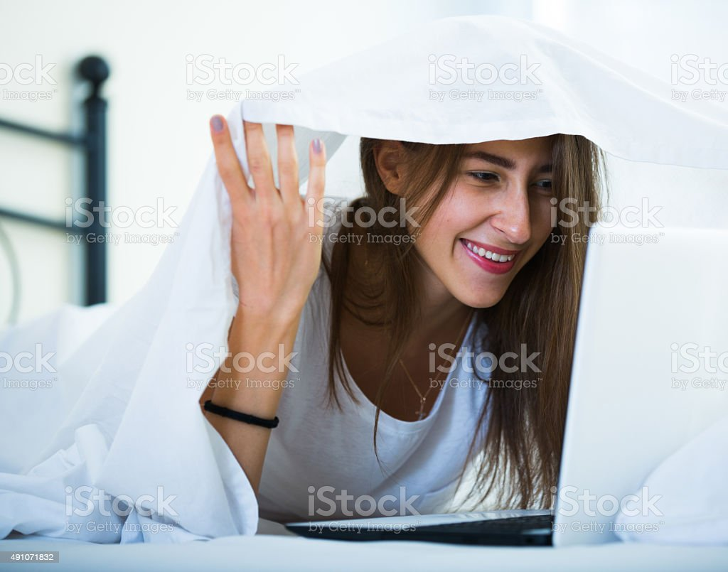 Teenage girl chatting online covered with blanket stock photo
